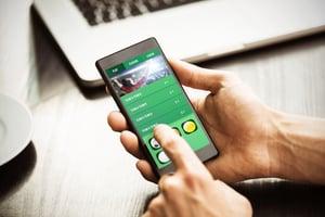 Hand holding smartphone against gambling app screen