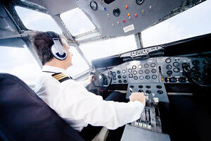 Pilot in an airplane cabin flying a plane