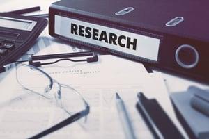 Carpeta de anillas con la inscripción Investigación sobre el fondo de la mesa de trabajo con material de oficina, vasos, informes.  Ilustración de tonos.  Concepto de negocio sobre fondo borroso.