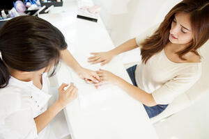 Woman doing a manicure at the beauty salon